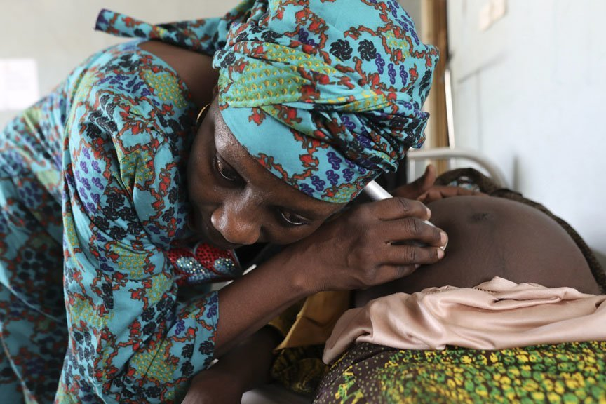 The head nurse at one of the CARE-supported clinics in Maiduguri checks on Fatima Abba Bukar. Photo: Josh Estey/CARE
