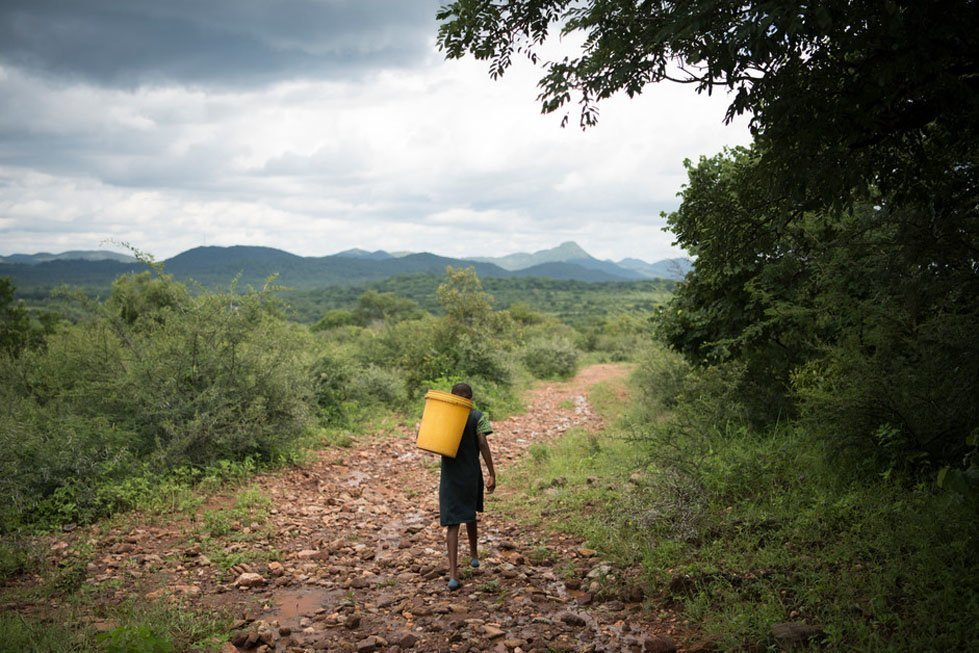 Precious carries a 20L bucket of water uphill 3kms back to her home, the round trip takes two hours. Photo: Alana Holmberg/CARE