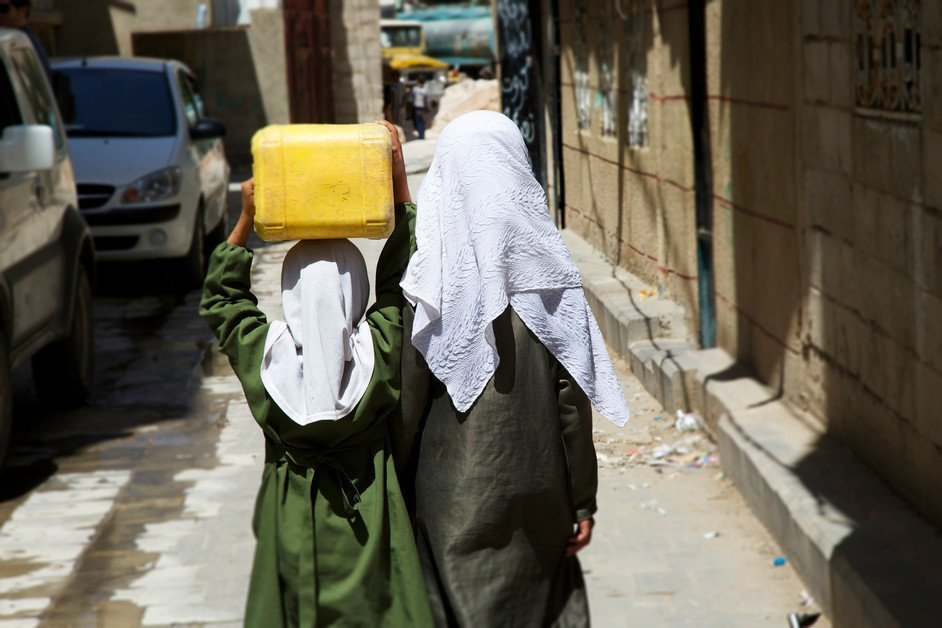 A woman and girl carrying water in Yemen