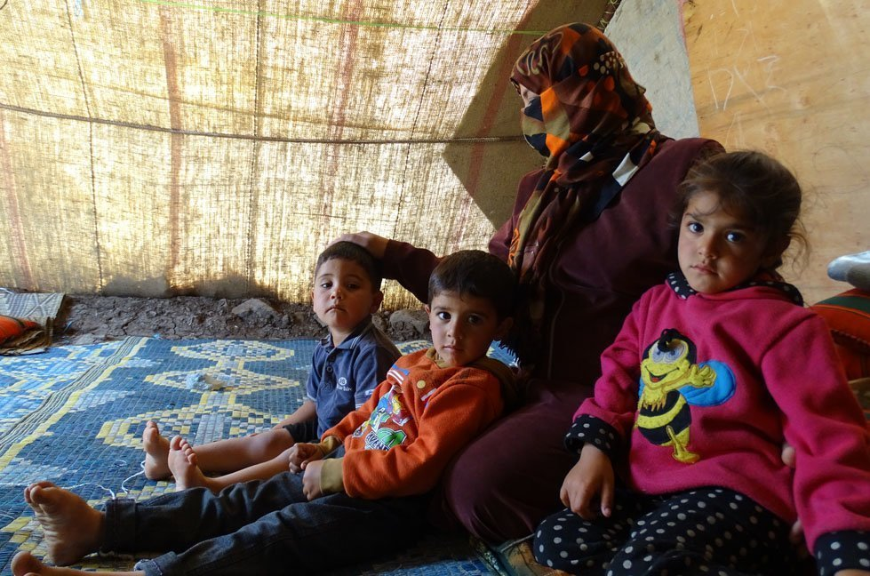Amani (name changed) with her three children inside Al-Rahma Camp
