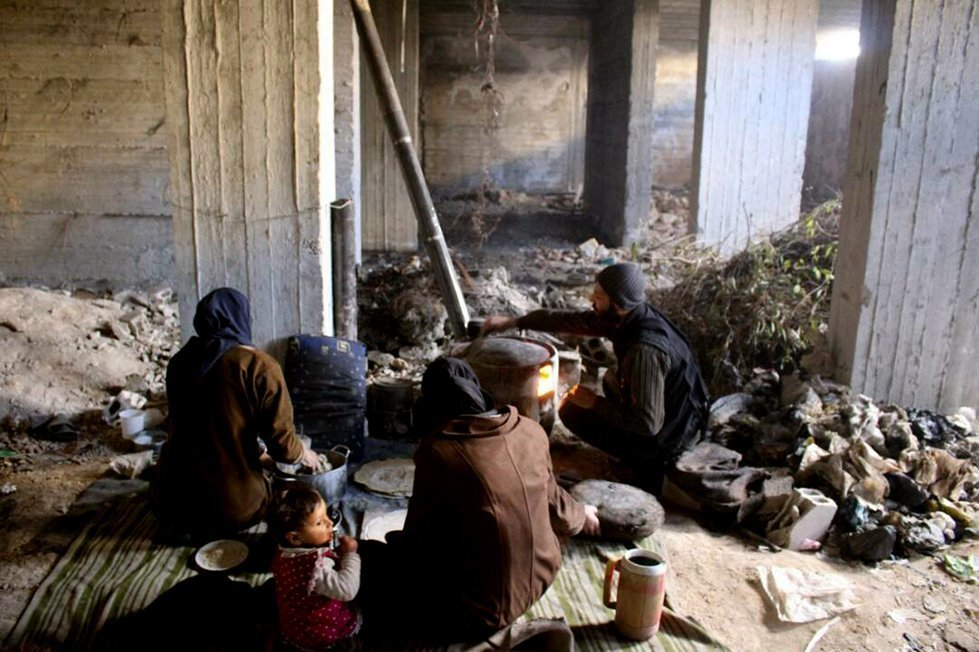 A family prepares to make a meal in a destroyed house, used as an emergency shelter, after being displaced from their home in Eastern Ghouta.