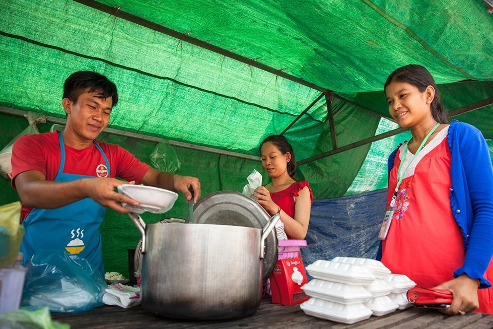 """Maly buys lunch from CARE's food vendor in front of her factory. """"Wejoined CARE's program to learn how to improve our cooking and hygiene"""", says Veasna, who has been cooking and selling his food in front of the factories for months. Phnom Penh, Cambodia. Mar. 14, 2018. © CARE / Erika Piñeros"""