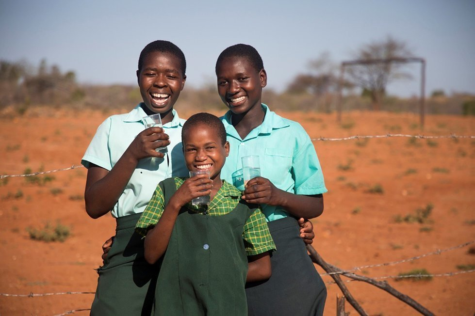 Girls enjoy clean water from a newly drilled borehole in Chivi District, Zimbabwe.
