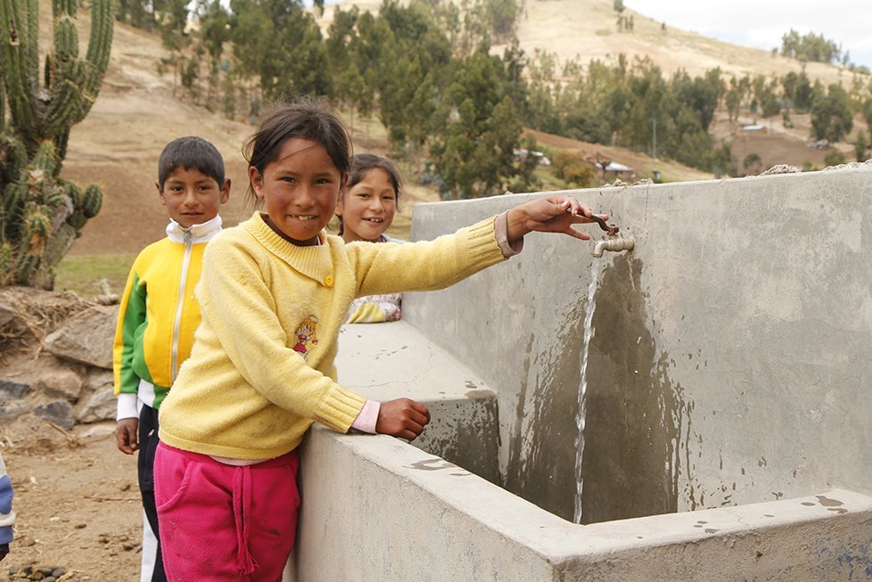 Children in a small rural community in Peru enjoy fresh, clean water from a tap installed by CARE.