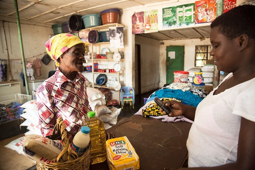 Tsungirirai Madziro (L), a CARE cash transfer project beneficiary, does a her monthly groceries using her e-wallet assisted by shopkeeper Viola Murambi in Zaka District, Ward 4 in Masvingo. Tsungirirai Madziro receives US$77 a month via a cash transfer to her SIM card from CARE which helps her cater for the nutritional needs of her family.