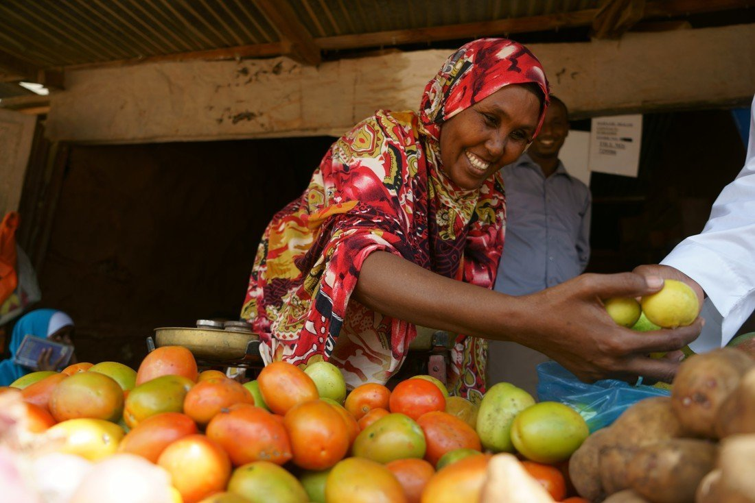 Hassan Hilowle is a refugee from Somalia living in Kenya in Dadaab camp. She was supported by CARE as a vulnerable woman to set up a market stall with a group of other women in Dagahaley camp, Dadaab. They have been running the business since 2011. They were given a freezer, blender and clothes to sell as well as technical support and entrepreneurship training. In a week they make an average of US $120-130 which is split between the 11 members. This money has helped Muhubo with school related costs, clothes for her children and additional food stuffs (like fresh fruit and veg) for the family. Her shop is a registered World Food Programme voucher vendor - a process which is run and managed by CARE and allows refugees with a monthly monetary sum to spend in pre-seleceted shops instead of food rations and allows them more choice and variety in what they eat. Photo by Lucy Beck/CARE