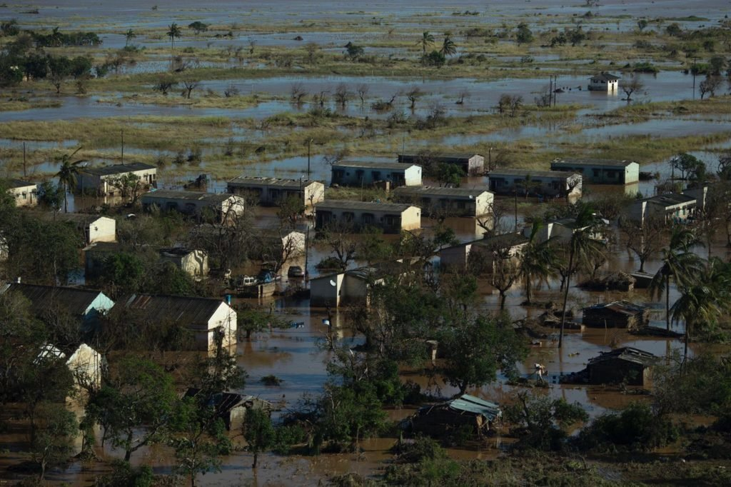 """It was the first day the sun was out. Helicopters and aircraft have arrived from all over the world. High-energy biscuits and bottles of water are being flown or sores to isolated villages, islands amongst the flood waters. What appears to be more of an ocean than land. Flying over the city you see the true destruction of the cyclone's power with residential homes torn open. As we fly off we see the sea, it has turned milk chocolate from all the rivers overflowing into its usual blue waters. Flying over farm land that is now flooded you see the occasional hut, crumbling in the flood waters. As we approach the """"island"""" of Guara Guara we see a white tent next to a field and a throng of people awaiting our approach. The town is now home to an estimated 1,300 people and more arriving every day from surrounded villages. It's the highest point in this area and is now home to everyone who has survived the flood waters Medical teams fly in and out each day. The people are asking for no more biscuits, they need food, rice and other necessities. We unload the high-energy biscuits and bottles of water with a group of young men helping to carry them off. The medical team has finished its day's work and replaces the cargo on the flight. This is an Indian Navy aircraft, they were practicing nearby when they got word for help and came. There are no doors on this ship and as we take off the kids wave to us, the houses on the outside of the village are still bathed in water reminding us how perilous the situation remains"""