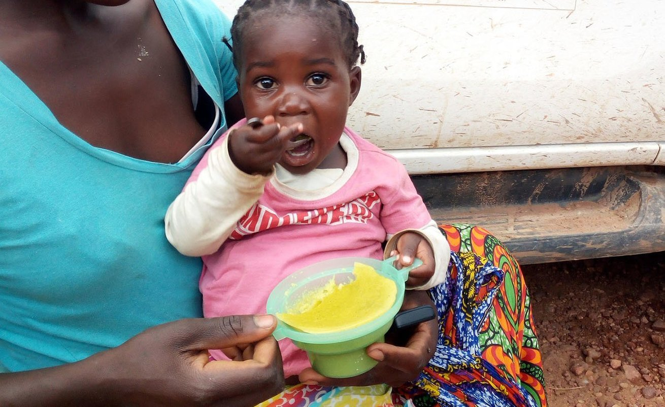 Little Mildred enjoying orange maize-pumpkin leaves porridge from a CARE food demonstration in Zambia.