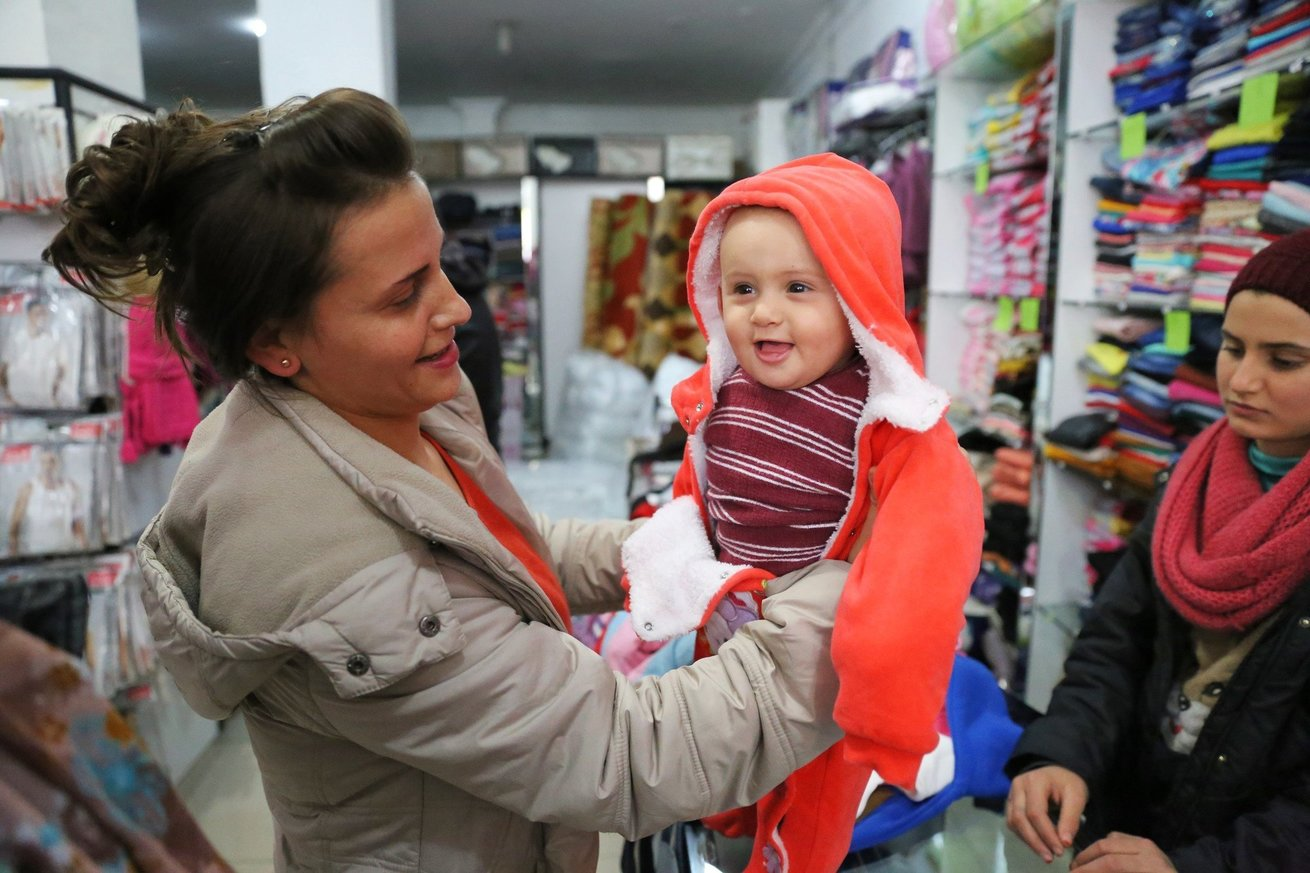 """CARE's winterization support teams started early in October 2016 to approach and aid households in two Turkish provinces.  """"The winter is very cold here,"""" says the mother of Eila, a 7-month-old in one of the CARE-participating shops providing household and winter items. """"I want to buy this outfit for Eila. She is always happy when she tries new clothes."""" © Khaled Mostafa/CARE"""