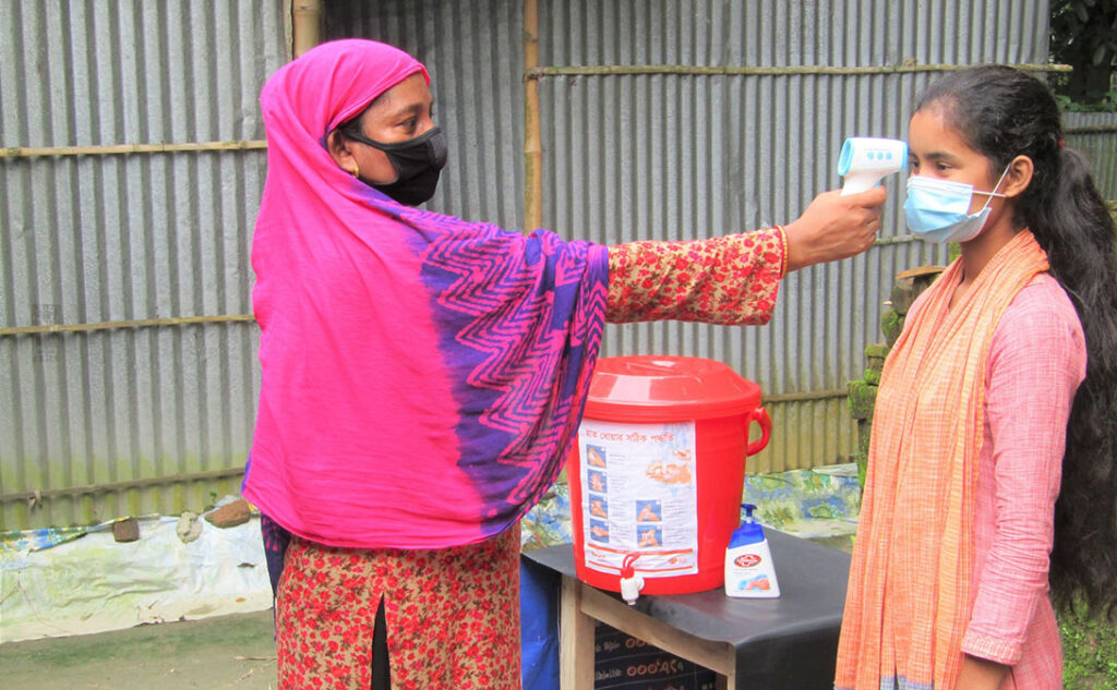 Temperature measurement of adolescent girls by thermal scanner in Bangladesh. Photo: Hillol Sobhan/CARE