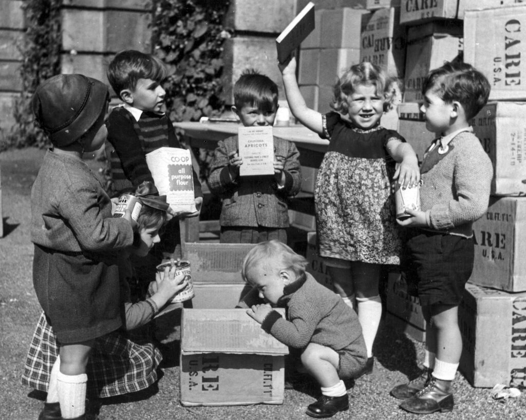 Young boys and girls displaying contents of CARE food package in Europe. July 1948.