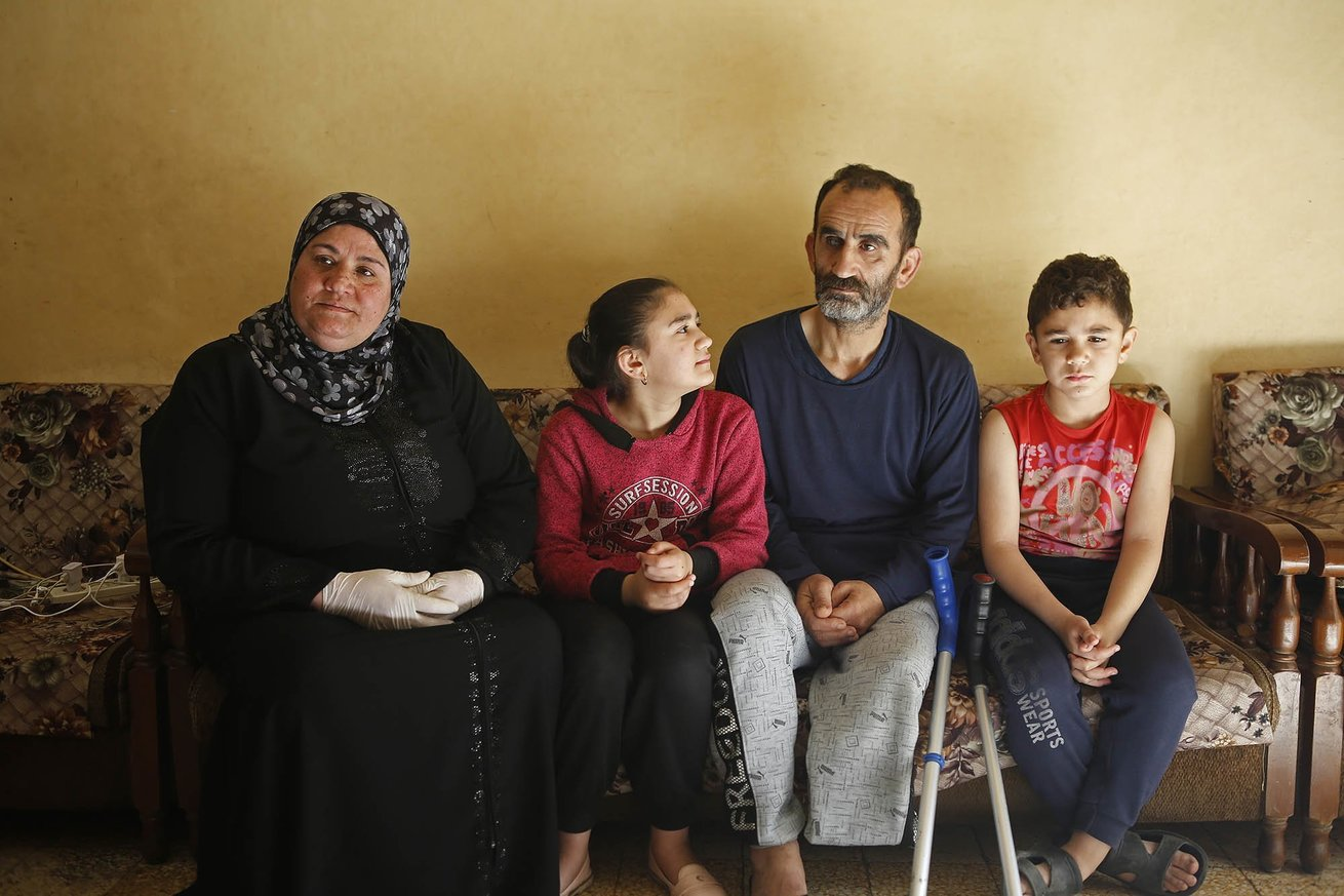 Fatima sits with her family in their small apartment in Tripoli, Lebanon