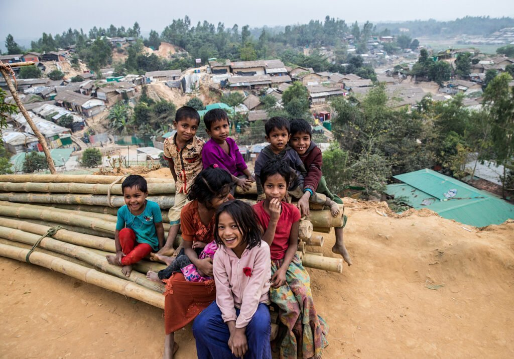 A group of children smile from a bamboo pile meant for home repairs, overlooking the Palangkhali refugee camp in Bangladesh..