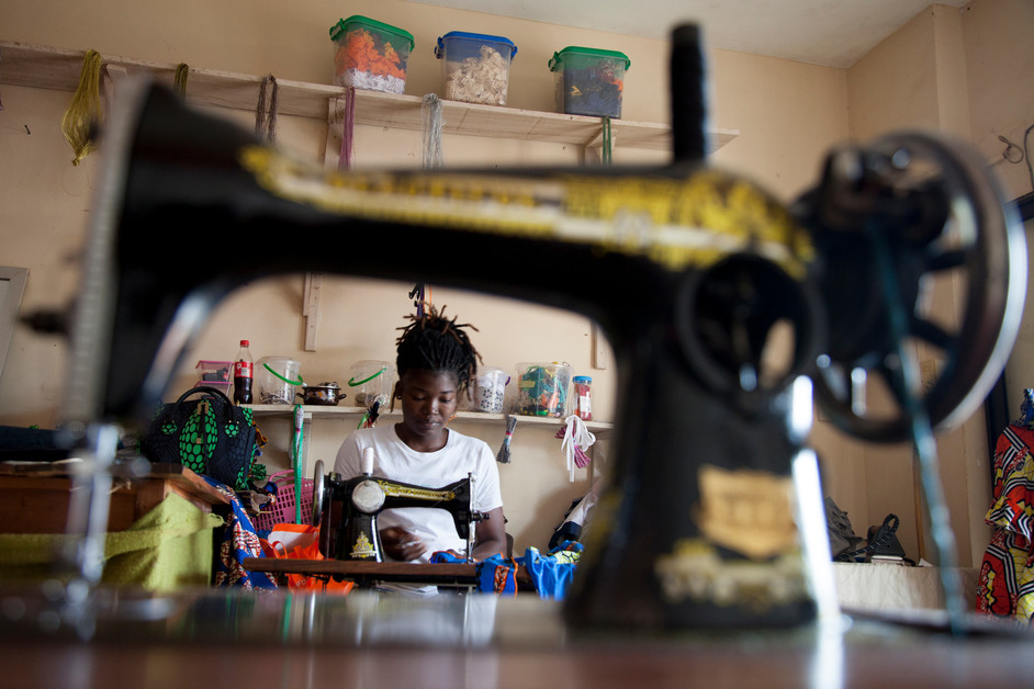 """Katraelle Johnson, 34 years old and mother of two children, had to retrain when Covid-19 arrived. Her grocery store was no longer receiving customers. Katraelle now makes children's clothing which she sells online. """"I wonder if we'll be able to go back to our old life,"""" she worries. """"I don't know if I can get my shop back. It's total uncertainty and anxiety."""" Porto Novo, Benin, 2020. Photo ©Laeïla Adjovi/CARE"""