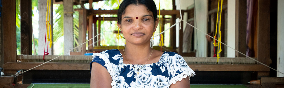 """<p style=""""margin-left:0cm;margin-right:0cm""""><span style=""""font-size:11pt""""><strong>Kirupalini Karunakaran, Weaver, Sri Lanka</strong></span></p>  <p style=""""margin-left:0cm;margin-right:0cm""""><span style=""""font-size:11pt""""><strong><em>&ldquo;I am father and mother to my son and now, thanks to my business, I can buy him what he needs.&rdquo;</em></strong><em>&nbsp; </em></span></p>  <p style=""""margin-left:0cm;margin-right:0cm""""><span style=""""font-size:11pt"""">Kirupalini, 32, runs her own weaving business selling beautiful handwoven garments to markets in the capital of Colombo over 300km away, as well as to buyers in other regions. </span></p>  <p style=""""margin-left:0cm;margin-right:0cm""""><span style=""""font-size:11pt"""">But behind her smile and this strong looking woman, there is a different story of daily struggle and a past clouded by growing up during Sri Lanka&rsquo;s 30-year civil war.&nbsp; Aged 19, she was hit by shrapnel from a bomb blast and has a visible welt in her arm as a daily reminder.&nbsp; Towards the end of the war there was major displacement within the country and Kiurpalini, her parents and her seven siblings had to quickly leave the safety of their own home, before it was razed to the ground.&nbsp; She adds: &ldquo;I can&rsquo;t count the number of places we moved to, sometimes it was two days here, a week there, but eventually we ended up in Menik Farm camp for six months.&rdquo;</span></p>  <p style=""""margin-left:0cm;margin-right:0cm""""><span style=""""font-size:11pt"""">It was at this camp where she married her school friend and she quickly fell pregnant.&nbsp; Sadly, he left her when she was only three months pregnant. Her son, now aged eight, has a brain injury and attends a special needs school.&nbsp;&nbsp; She glows with pride when she speaks about her son and pulls out her phone to show pictures, adding: &ldquo;I am father and mother to my son and now, thanks to my business, I can buy him what he needs.&rdquo;&nbsp; She has also become President of the Spe"""