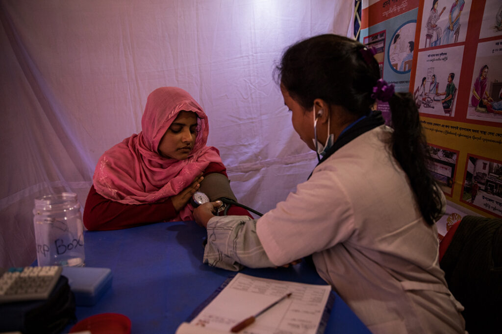 A Rohingya woman being diagnosed by a CARE Bangladesh health worker at a mobile health clinic in Bangladesh.