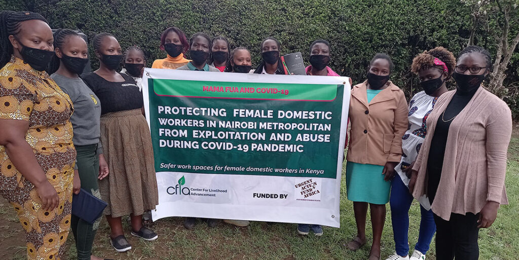 """Mama Fuas group leaders gathered holding up a banner that reads """"Protecting female domestic workers in Nairobi metropolitan from exploitation and abuse during COVID-19 pandemic. Safer spaces for female domestic workers in Kenya."""" Photo: Center For Livelihood Advancement (CFLA)"""
