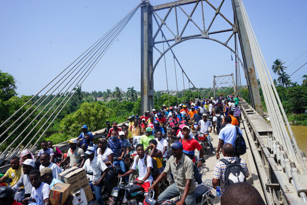 People photographed on and near the Dumarsais Estime bridge, where pedestrians and some smaller vehicles can pass, but not truck, in late August, 2021, after a 7.2 earthquake wrecked havoc in Haiti. The bridge connects the town of Jèrèmie to the rest of the country's highways. © 2021 CARE