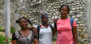 """Pamphile Fabiana, a CARE village agent who lives in the town of Latibolière, in the 4th section of Basse Guinaudé, speaks about what she and her community lost in the August 2021 7.2 magnitude earthquake that caused massive loss of life and property in southern Haiti. Fabiana (in pink shirt) is pictured w other members (names not known) of her community near a damaged school in late August 2021. """"We have lost all our possessions, such as: our houses, our churches, our schools, our health centers, all our animals, some members of our families are victims, their feet are broken,"""" She said (using Google translate)."""