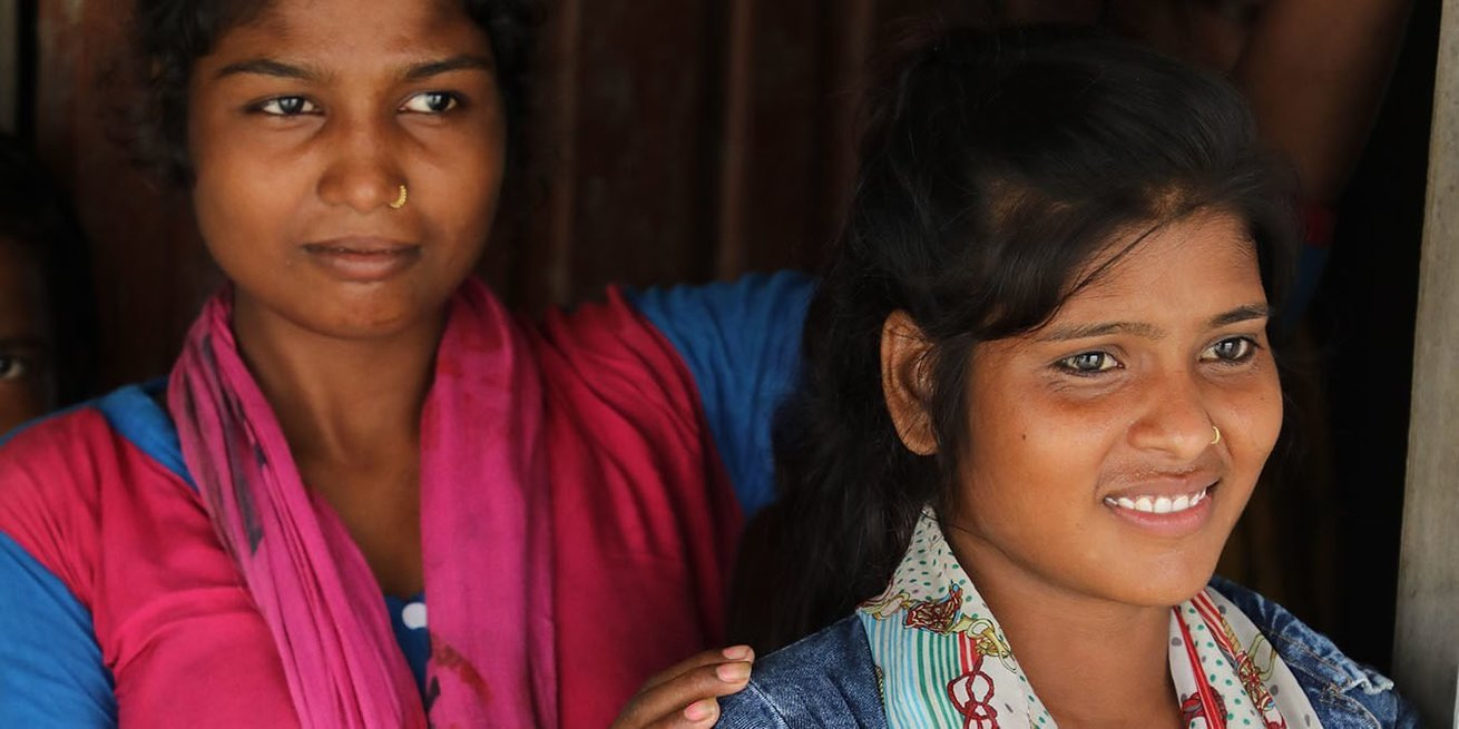 Two members of a CARE girls' collective gather before their meeting. Sadhana, in the foreground, stopped her own child marriage and then helped others in her school and community understand why and how child marriage can be prevented.