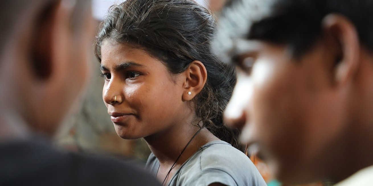 A young girl participates in a discussion with boys in her community about sexual harassment and how boys and girls can work together to prevent it.