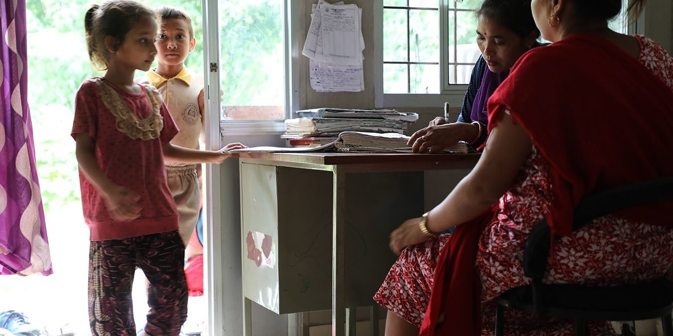CARE-trained birth attendant Muna Bayalkoti, in purple, receives patients at a health clinic in Gankhu village. CARE helped establish this facility after the earthquakes of 2015 and now the community sees zero home births.