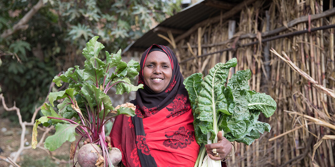 Sergut Abera, mother of three, showcases part of the large harvest from her household garden. She was trained on maternal nutrition and feeding practices as part of GROW.