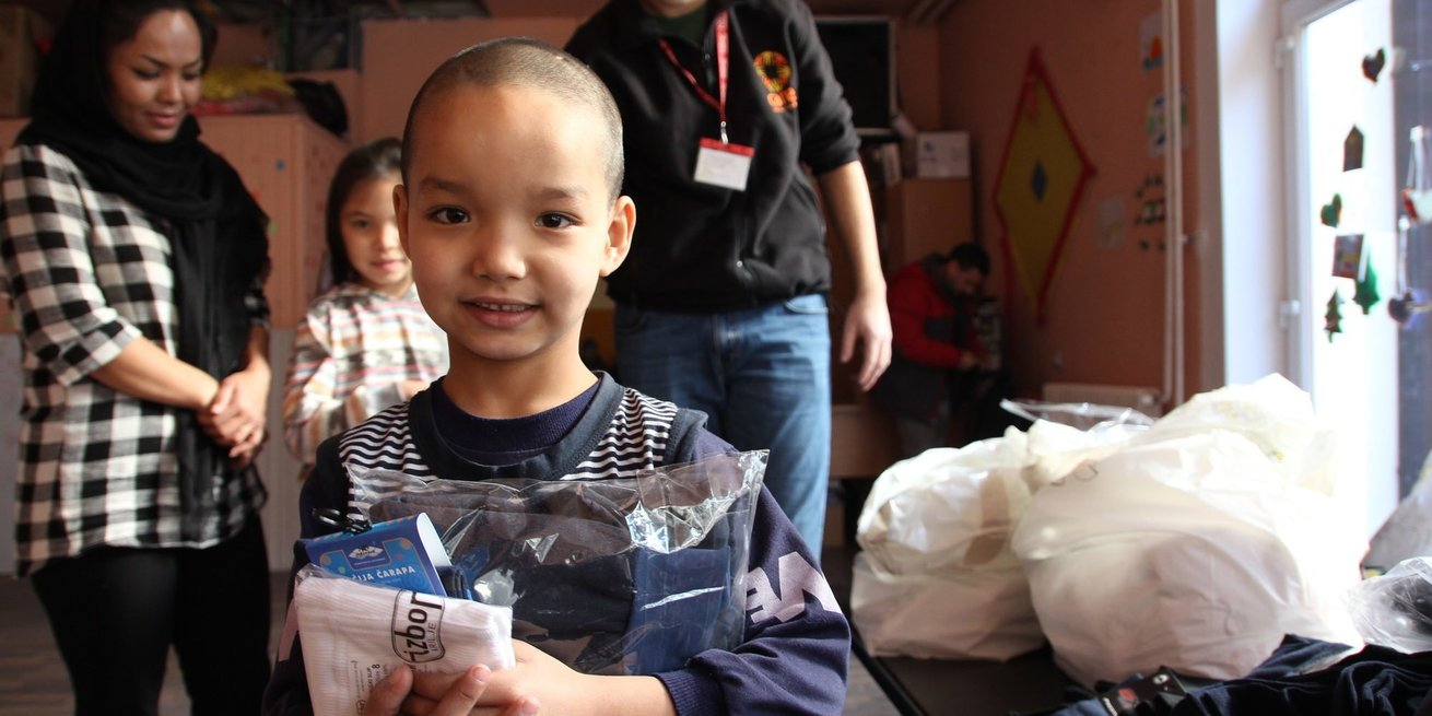 A little boy with his clothes he just received from a CARE/NSHC distribution. Distribution of winter clothes to refugees in Bogovadja, in Western Serbia. 240 people are housed in a refugee camp here where CARE's partner NSHC provides ongoing support. Today, families receive a CARE package of different items including warm jackets, pants, sweatshirts, gloves, bonnets, underwear and other items to keep them warm during the winter.