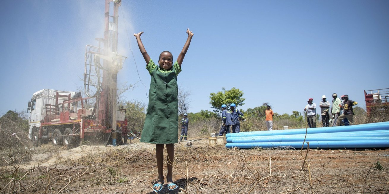 Precious is overjoyed my seeing water come out of a new borehole CARE gave her village in Zimbabwe