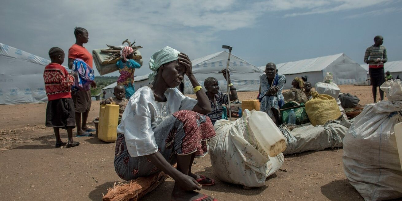 Refugees, carrying their few remaining possessions, wait in the transportation area of the Imvepi Refugee Settlement in Uganda in 2019