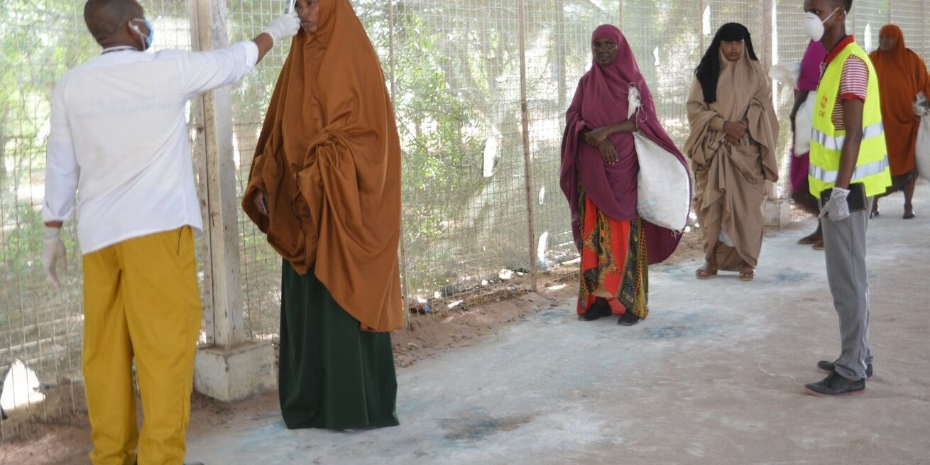 Women line up to have their temperature checked while maintaining social distance in Kenya's Dadaab refugee complex